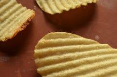 Chips met geribbeld of golven op bruine oppervlakte royalty-vrije stock foto