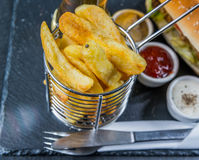 Chips in a metal basket, a background crusty white bread with se Royalty Free Stock Photo