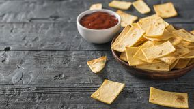 Chips from a Mexican tortilla with tomato sauce on the black wooden table. Royalty Free Stock Image