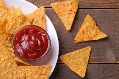 Chips. Nachos on a white plate with red sauce on a brown wooden background. View from above stock images