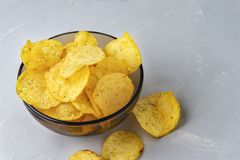 Chips with onions. A bowl of potato chips on a grey background. Chips with onions. A bowl of potato chips on a grey background stock photo