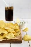 Chips op een scherpe raad met het onderdompelen van saus en drank Stock Foto's