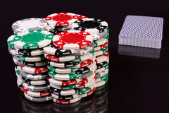 Chips and a pack of cards. There are chips of gambling and a pack of cards in the picture. The background is black Stock Photo
