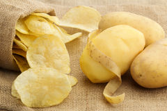Chips and peeled potato. On a jute texture Royalty Free Stock Photos