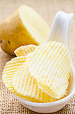 Chips and peeled potato. Chips and peeled potato on a sack background royalty free stock images