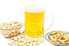 Chips, pistaches en glas bier op wit Stock Foto's