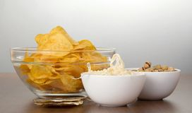 Chips, pistachios, dried squids and salty fish Stock Photo