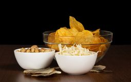Chips, pistachios, dried squids and salty fish Royalty Free Stock Photo