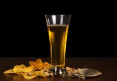 Chips, pistachios, salty fish and beer glasson Royalty Free Stock Photography