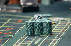 The chips on the playing field. Detail of a green roulette table with some numbers Stock Photo