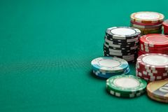 Chips for playing poker on green gaming table. Concept gambling and addiction royalty free stock images