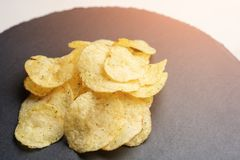 Chips from potato on the tray with tinted sunlight.  stock images