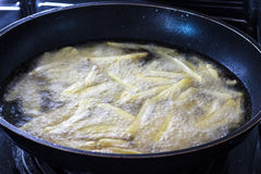 Chips, potatoes frying in the pan in olive oil Stock Photography
