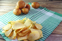 Chips and raw potatoes. Potato chips in bowl and fresh potato Stock Photography