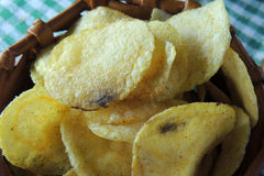 Chips and raw potatoes. Potato chips in bowl and fresh potato Royalty Free Stock Photography