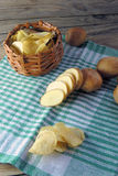Chips and raw potatoes Royalty Free Stock Photos