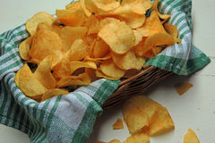 Chips and raw potatoes. Potato chips in bowl and fresh potato Royalty Free Stock Image