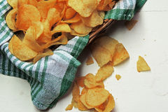 Chips and raw potatoes. Potato chips in bowl and fresh potato Stock Image