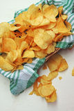 Chips and raw potatoes. Potato chips in bowl and fresh potato Stock Photo