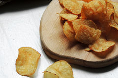 Chips and raw potatoes. Potato chips in bowl and fresh potato Royalty Free Stock Photo