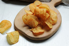 Chips and raw potatoes. Potato chips in bowl and fresh potato Royalty Free Stock Photos