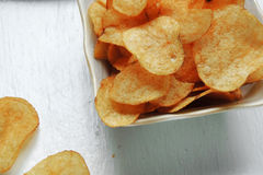 Chips and raw potatoes. Potato chips in bowl and fresh potato Stock Photos
