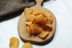 Chips and raw potatoes. Potato chips in bowl and fresh potato Royalty Free Stock Images
