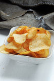 Chips and raw potatoes. Potato chips in bowl and fresh potato Stock Images