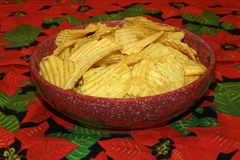 Chips In Red Spotted Dish. Heap chips in red spotted dish on a floral tablecloth Royalty Free Stock Photography