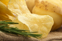 Chips, rosemary and raw potato. Close up of chips, rosemary and raw potato on a jute background stock images