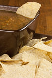 Chips and Salsa. Corn tortilla chips around a brown bowl of homemade salsa Royalty Free Stock Images