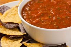 Chips and Salsa. A bowl of organic salsa and a plate of corn tortilla chips Stock Images