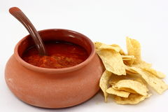 Chips and Salsa. A terracotta dish filled with red salsa sitting next to a pile of tortilla chips and photographed on a white background Royalty Free Stock Images