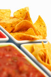 Chips with Salsa Dip. Some cheese flavored tortilla/Nacho chips on snack bowls together with salsa sauce. Shallow DOF, focus on the far end Stock Photo