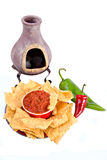 Chips, salsa and peppers. Mexican oven with candles and tortilla chips, salsa, red and green peppers isolated on white background Royalty Free Stock Images