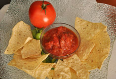 Chips and salsa platter. Delicious fresh salsa with corn chips and tomato on interesting platter Royalty Free Stock Images