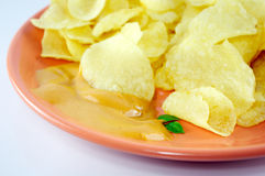 Chips and sauce. Chips with sauce in a plate on white background Stock Images