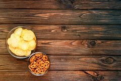 Chips, snacks in glass plates on the background of a wooden table. Beer snacks. food in front of the TV. fans stock photography