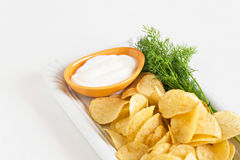 Chips with sour cream and dill sauce isolated royalty free stock photography