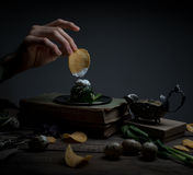 Chips, spinach, sauce, vintage book. man`s hand on a dark background Royalty Free Stock Photography