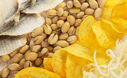 Chips, squids, pistachios and salty fish Royalty Free Stock Images