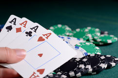Chips stack and four of kind poker combination on a green background. Stock Photos