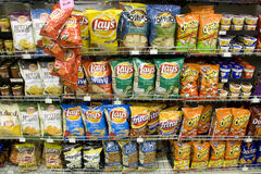 Chips on store shelves. Different brand and flavor of chips for sale in a supermarket. Potato chips are the most popular junk food in America. A lot of people Stock Images