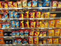 Chips on store shelves. Various chips of different flavors on store shelves Stock Images