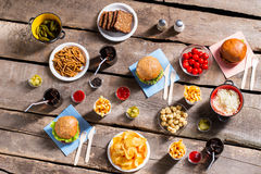 Chips and tomatoes with burgers. Royalty Free Stock Image