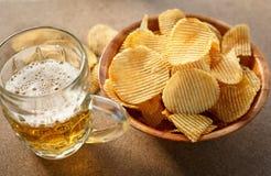 Chips und Bier auf einem Holztisch stockfotos