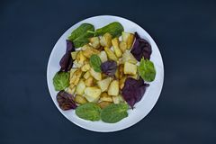 Chips with various lettuce leaves on a dark wooden background. View from above royalty free stock photography