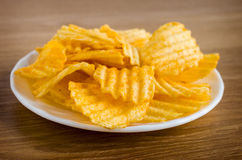 Chips are in white plate. On a wooden table Stock Images