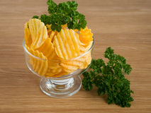 Chips are in white plate. On a wooden table Stock Photography