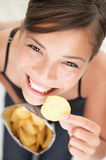 Chips woman. Woman eating chips. Beautiful young woman eating potato chips / crisps royalty free stock photos